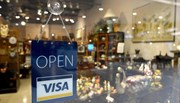 Shop's glass door with sign stating open and uses VISA